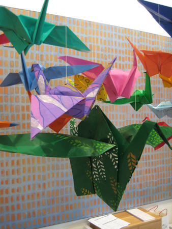 The smallest cranes were made from traditional origami paper. I was  able to purchase nicely colored and printed paper up to 1' X 1', but to  get the colors and prints I wanted for the larger cranes I had to paint  the paper myself. The largest crane in the middle was made from a 4' x  4' sheet of paper that I painted and stenciled. All the other cranes in  this shot were hand painted as well.