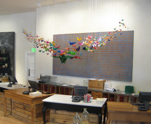 I'm not sure how many origami cranes I made in the end, but it took  about a week to make them all and then a couple more days to hang each  by an individual string from the ceiling. The shape of the installation  echoes the shape of the wings on all of the cranes. And as you look from  the tips to the center, the cranes increase in size.