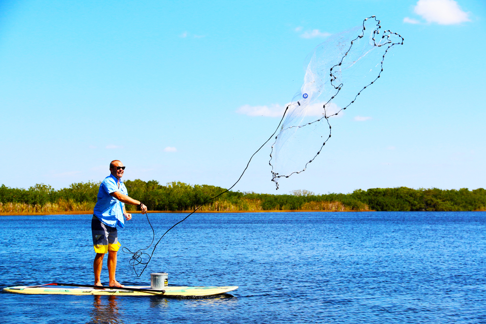 Mike throwing his castnet from the paddleboard
