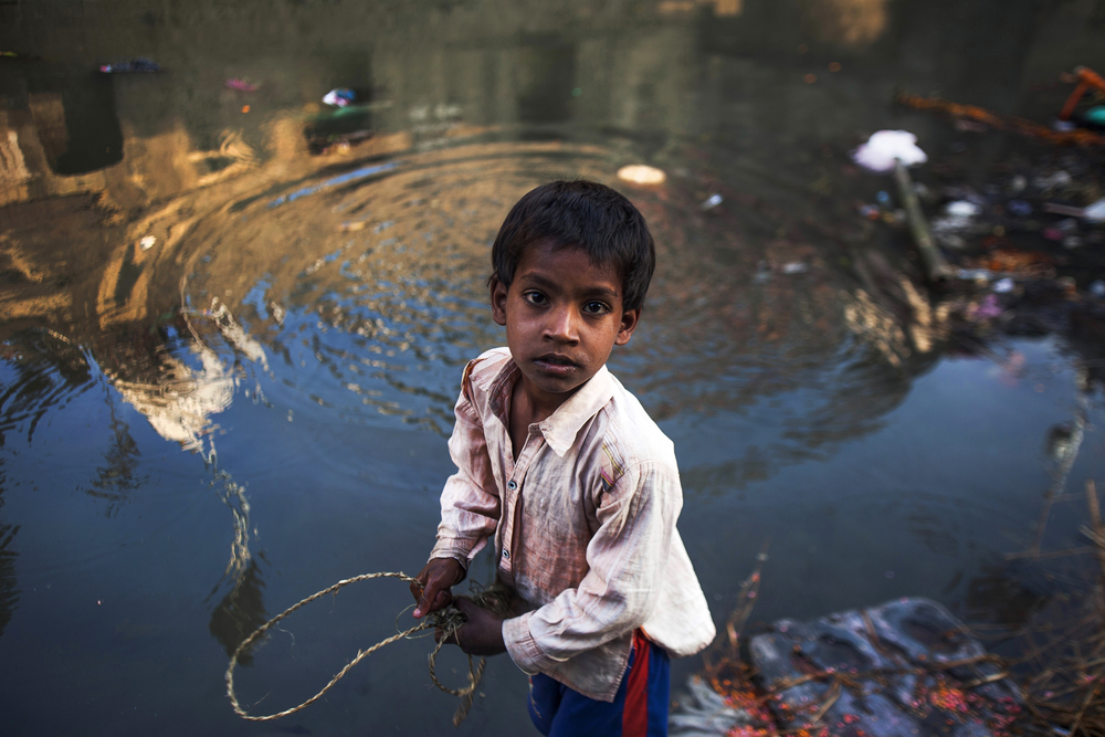 08_MAGNET_An orphan boy uses a magnet to collect left over offerings from purification rituals.jpg