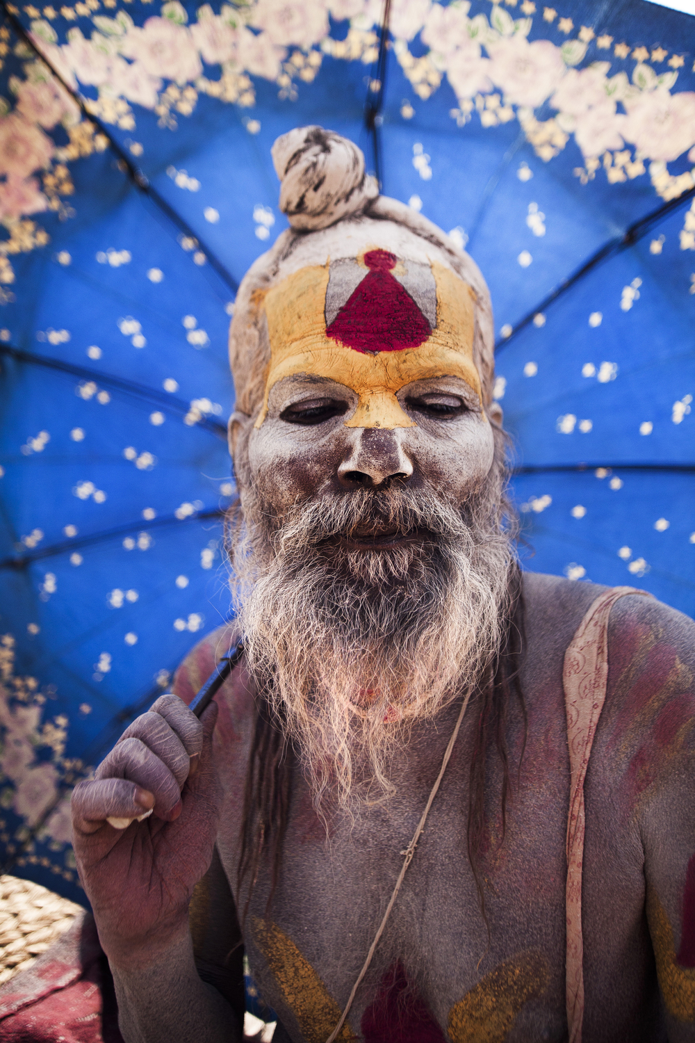 A sadhu shields himself from the midday sun.