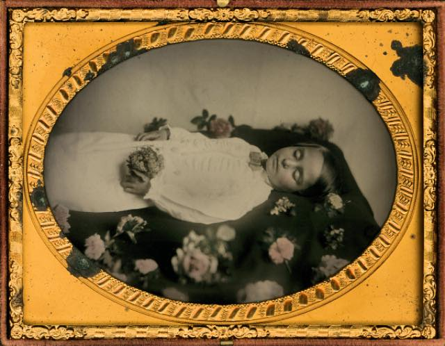 """Surrounded by Flowers"" (1860), quarter-plate ambrotype, hand colored, 4.75″ x 3.75,"" a postmortem photograph of a young boy in a burial gown (courtesy Thanatos Archive)"