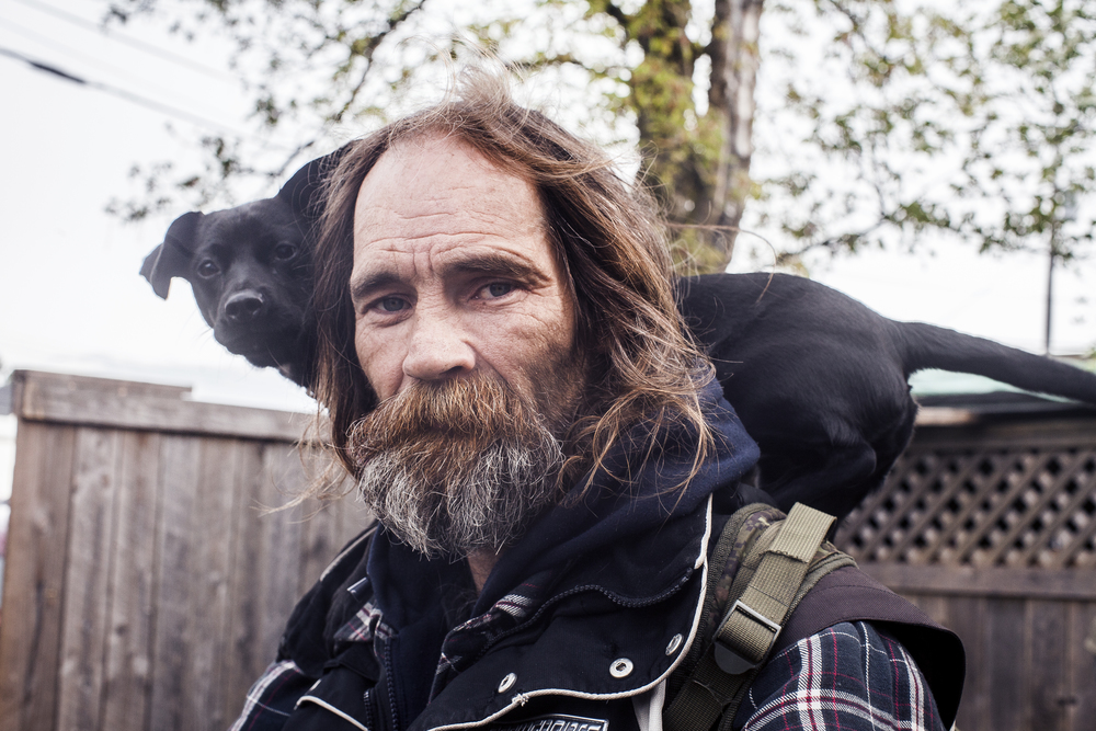A portrait of Rick and his puppy on a bicycle in Marcia's backyard.