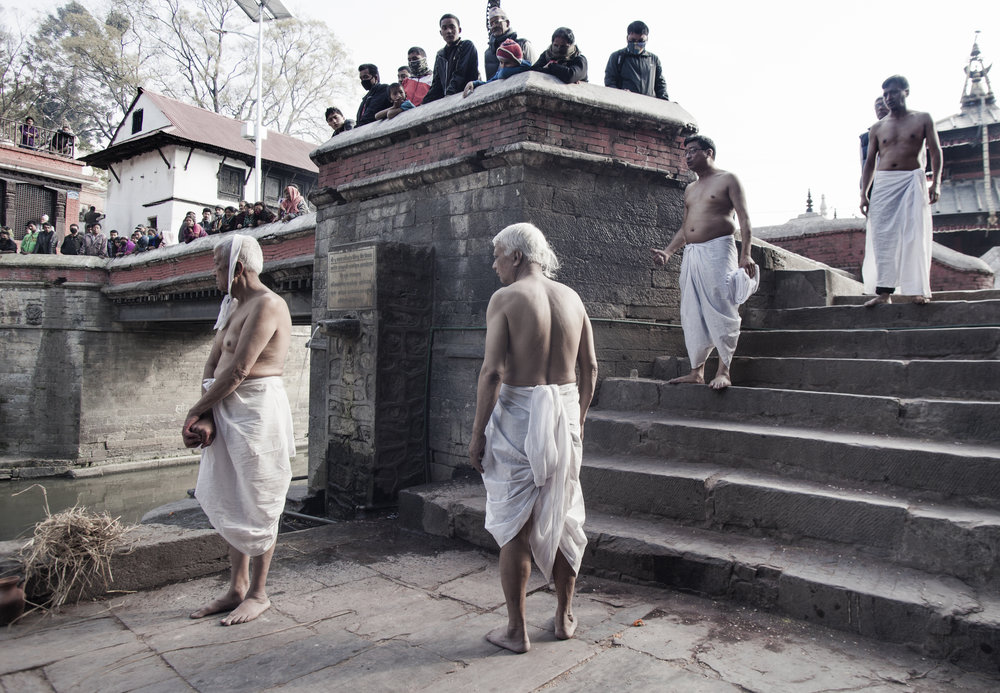 Four brahmin brothers, at the northern ghats reserved for higher castes, moments before cremating their father. The eldest will light the body via the mouth. A few minutes after the pyre is lit, he will then perform Kapal Kriya, which involves cracking the skull with a bamboo stick to encourage the soul to depart.