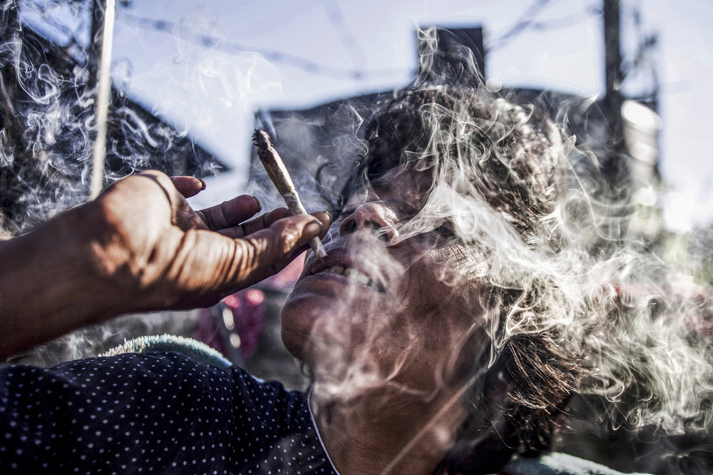 38-year-old Rupa smoking in her bed above Pashupatinath's northern cremation ghats.