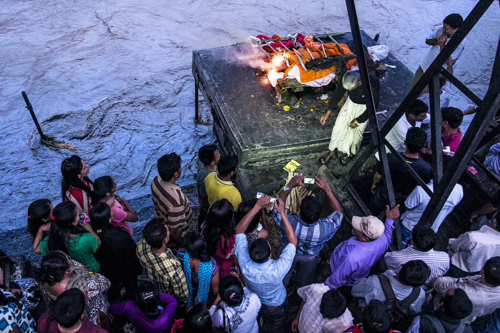 Relatives film the beginning of a cremation of an elderly man at Pashupatinath's northern ghats.