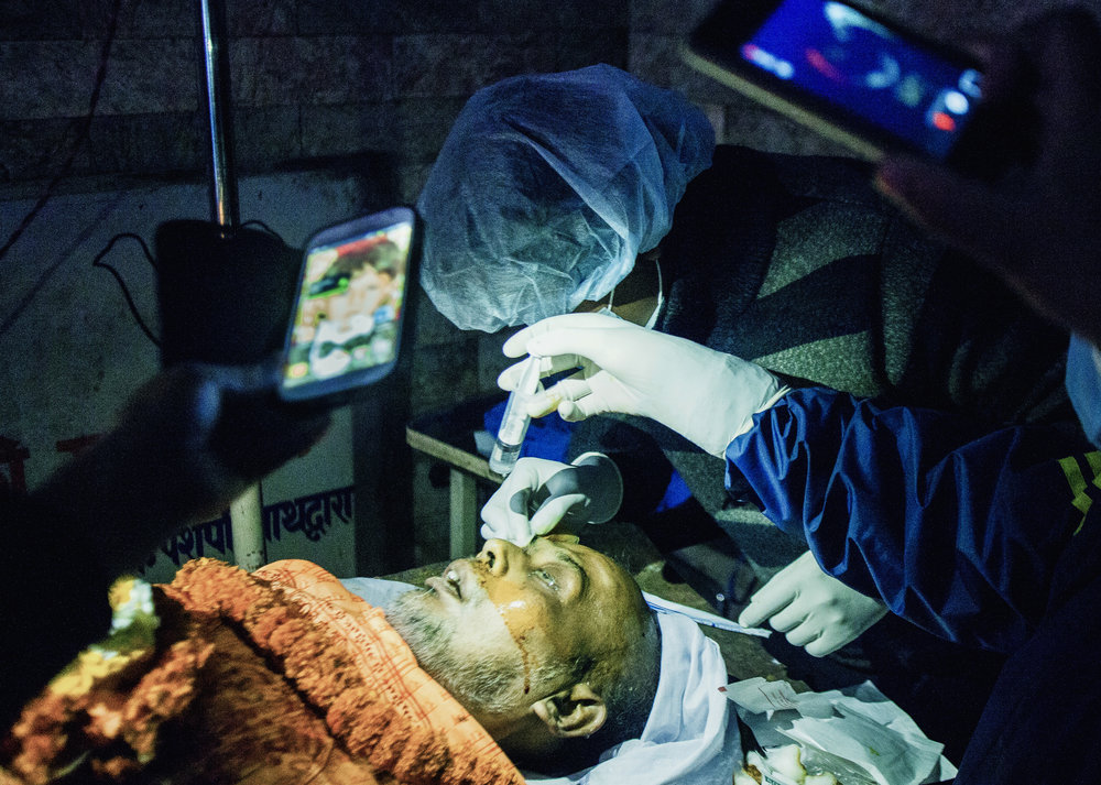 Friends and family use the torches on their phones to shed light on a cornea extraction after a power outage. The extraction is performed by student doctors directly after purification rituals in a tiny room next to the northern cremation ghats.