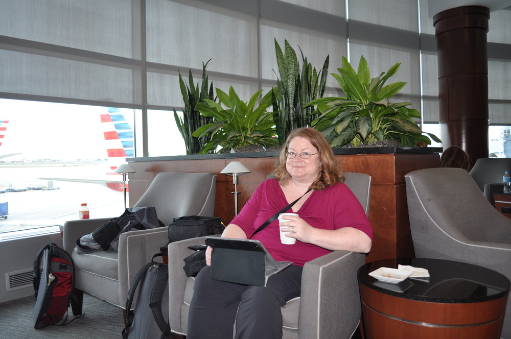 Dianne with a cup of coffee and Facebook in the American lounge at CLT
