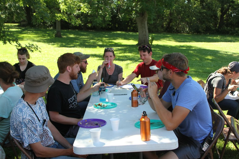 Jacob Midkiff a 2nd Year MFA student (2nd Left) and Megan Fitzgerald a MFA thesis student (Center) sit on location enjoying catering.