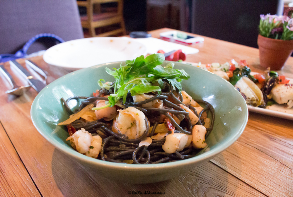 Squid ink spaghetti with seafood, arugula, preserved lemon