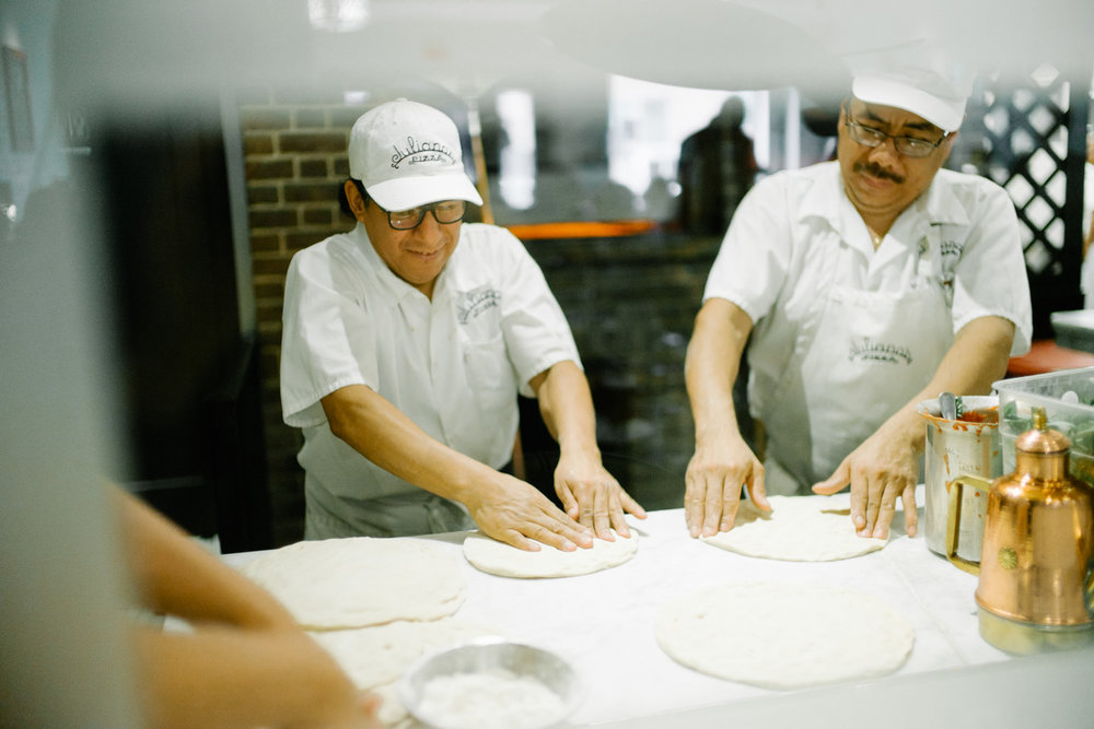 Open kitchen showing the chefs at work kneading pizza dough