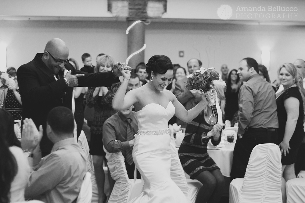 The bride and groom make their entrance during the reception at the Italian American Community Center.