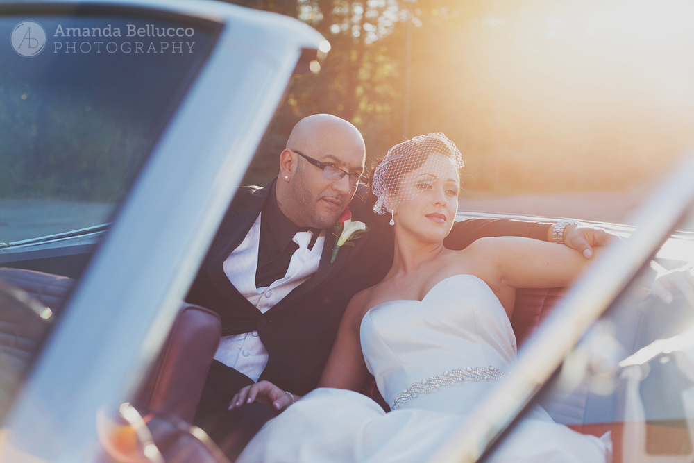 The bride and groom pose for wedding photos in a vintage convertible at the Italian American Community Center.