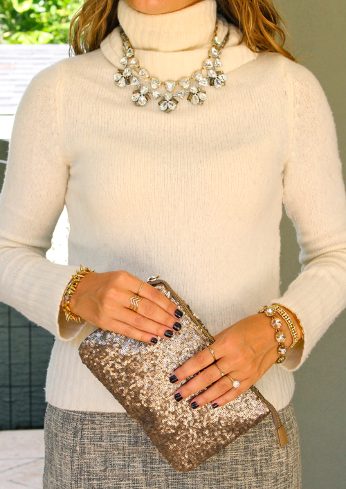 Ivory turtleneck sweater with statement necklace and sequin clutch
