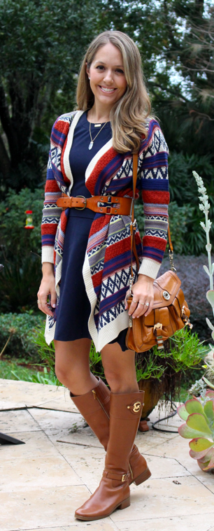 Belted sweater over navy dress with cognac boots
