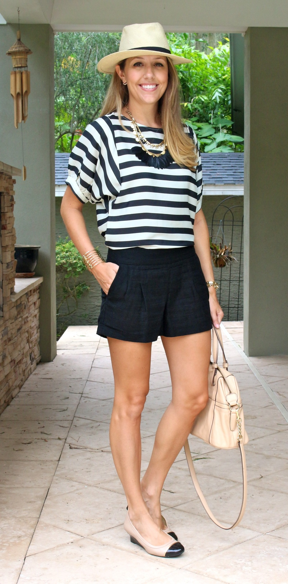 Striped top, Panama hat, black shorts, feather necklace