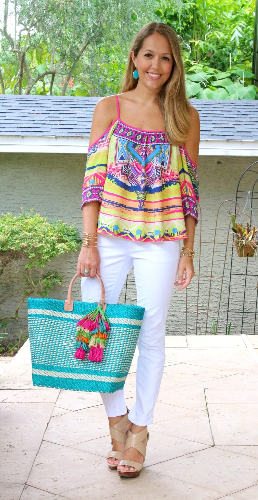 Colorful top, white jeans and straw tote