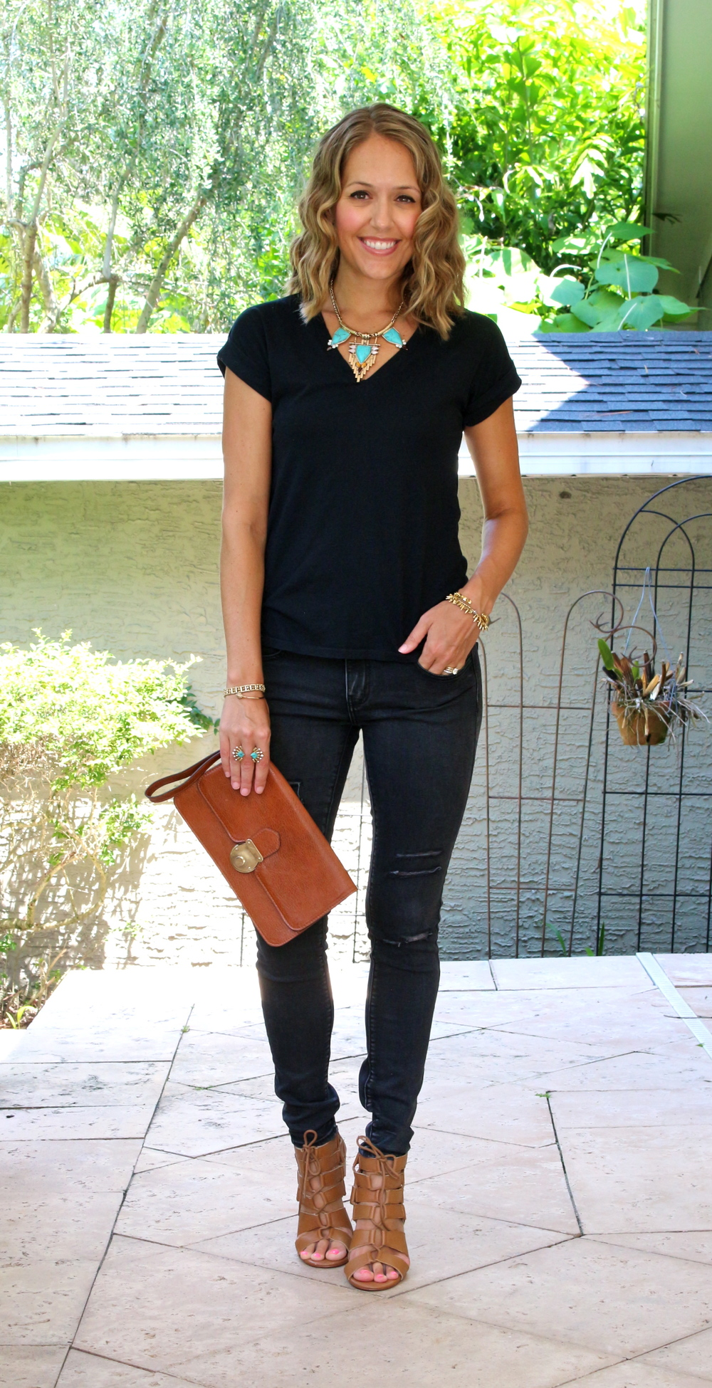 Black tee, black jeans, cognac accessories