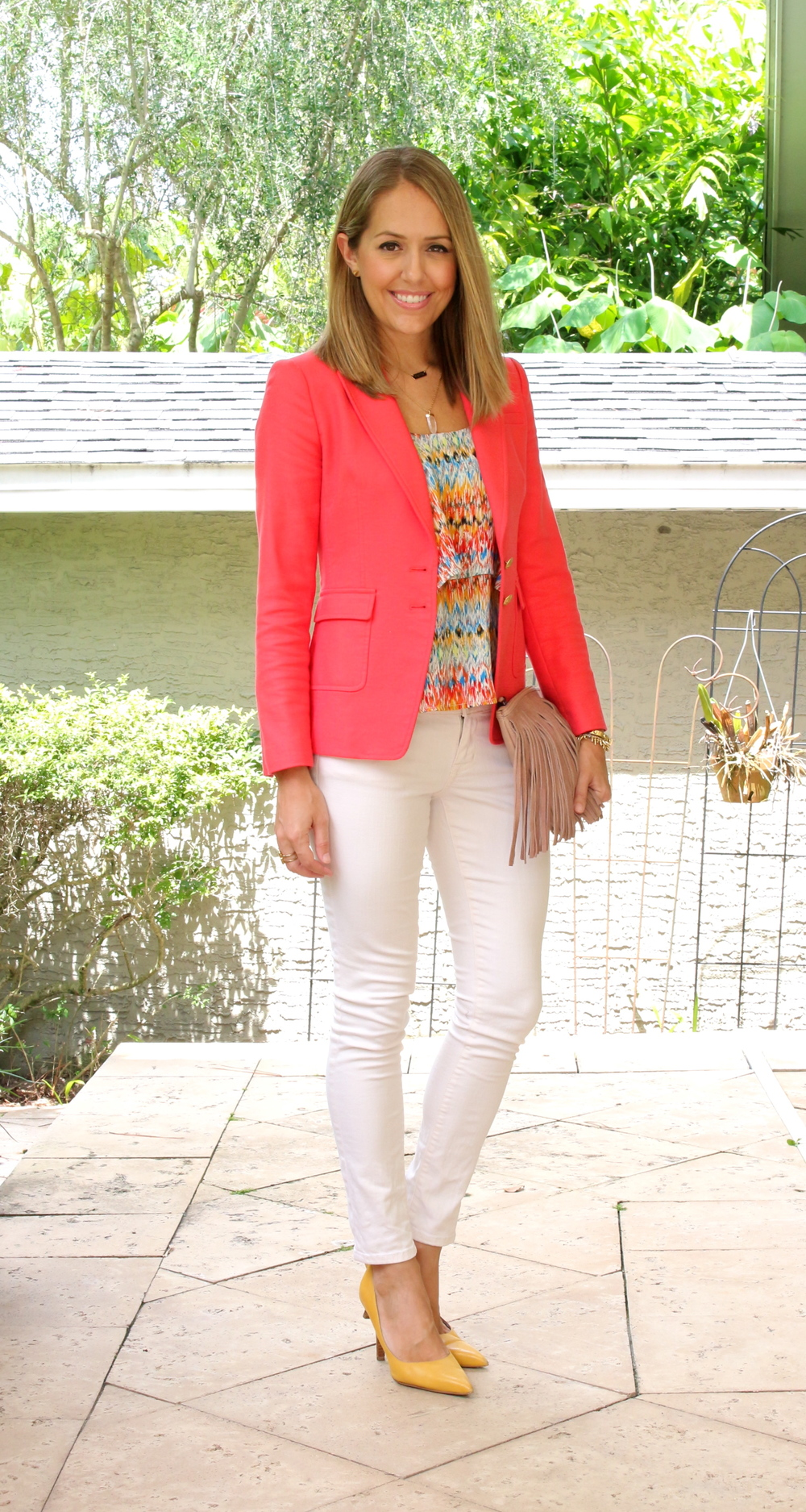 Coral blazer, ivory jeans, yellow pumps, fringe clutch
