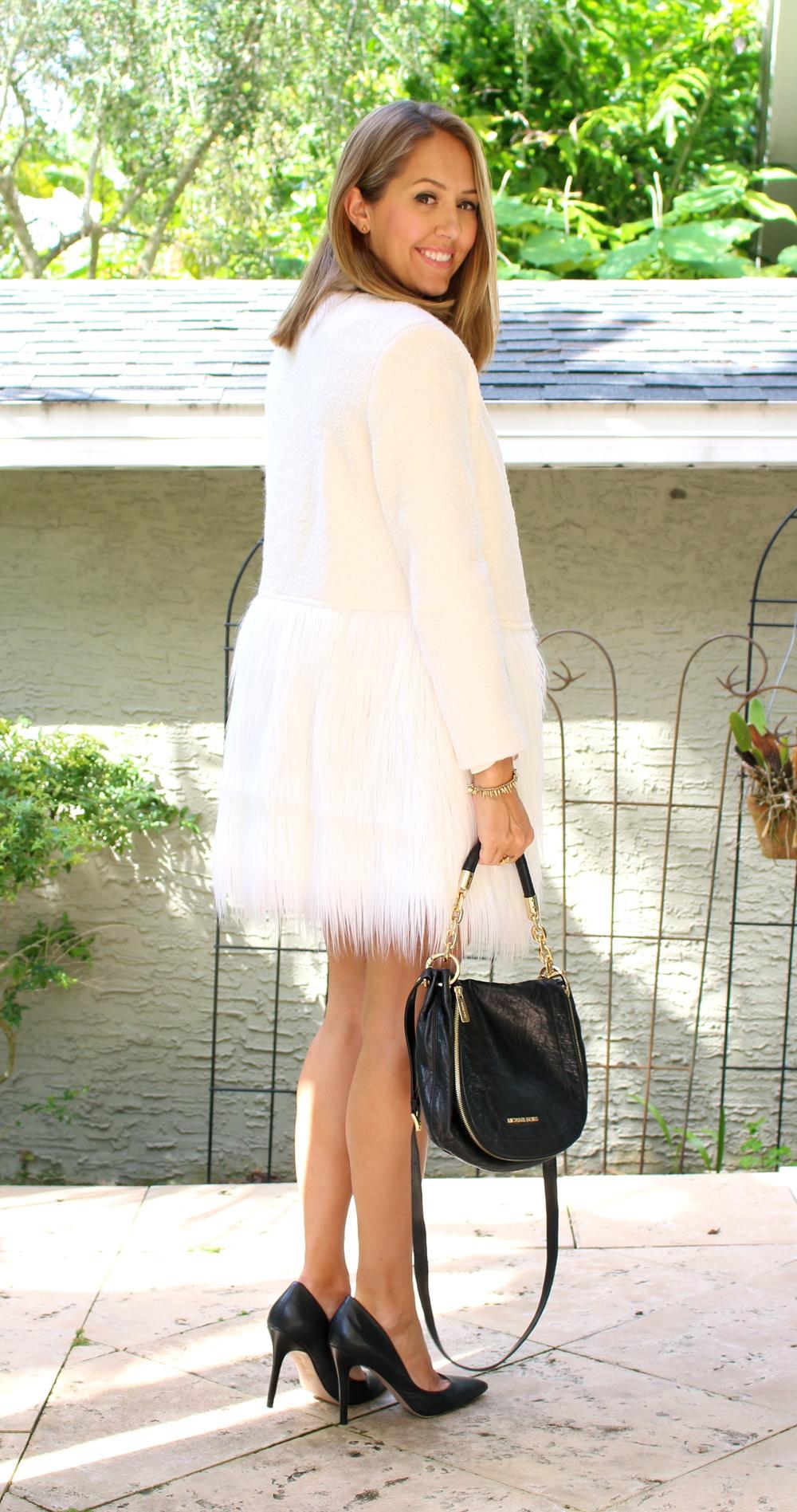 White faux fur coat, black pumps