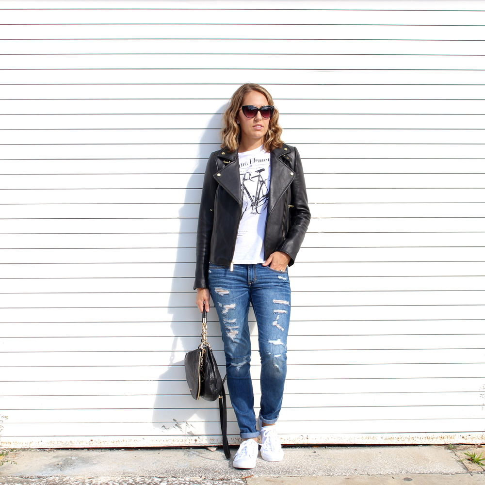 Black leather jacket, distressed jeans, white sneakers