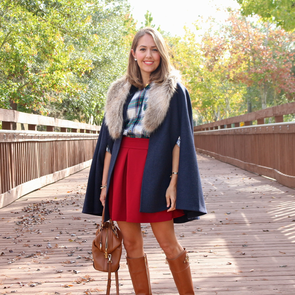 Navy cape, plaid top, red skirt, riding boots