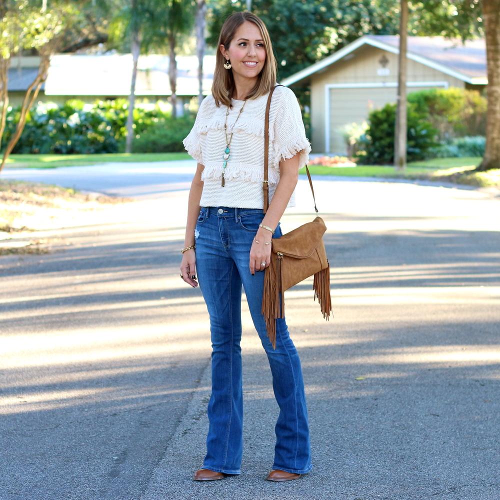 Fringe sweater, flare jeans, fringe clutch