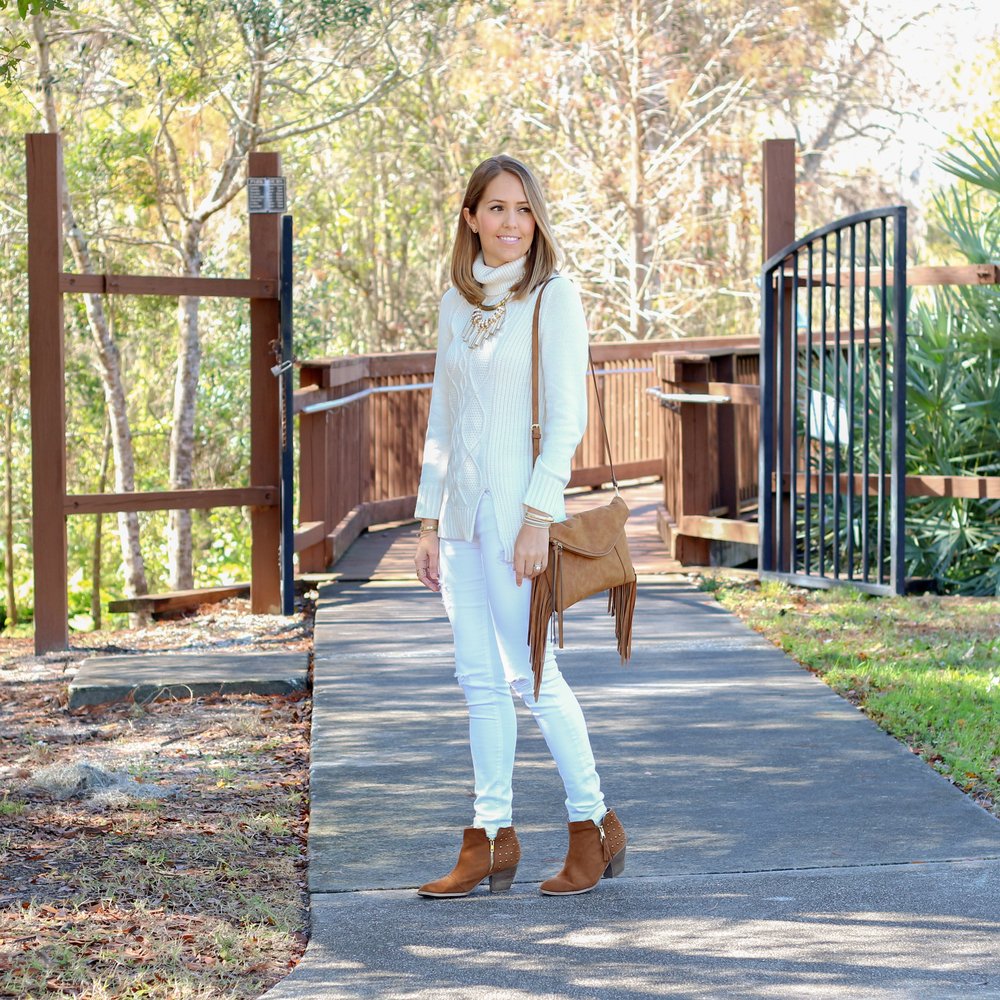 Winter white turtleneck and jeans with brown boots and purse