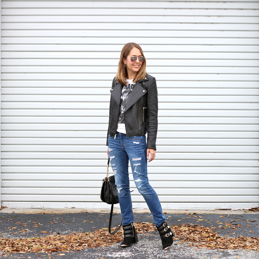 Leather jacket, white graphic tee, distressed jeans