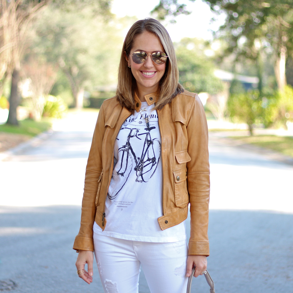 Tan leather jacket, white graphic tee, white jeans