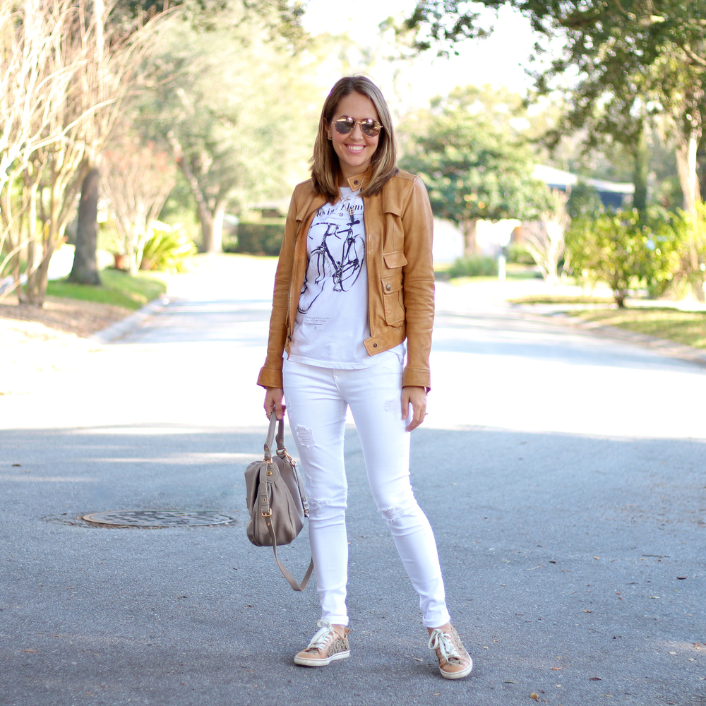 Tan leather jacket, white graphic tee, white jeans, sneakers