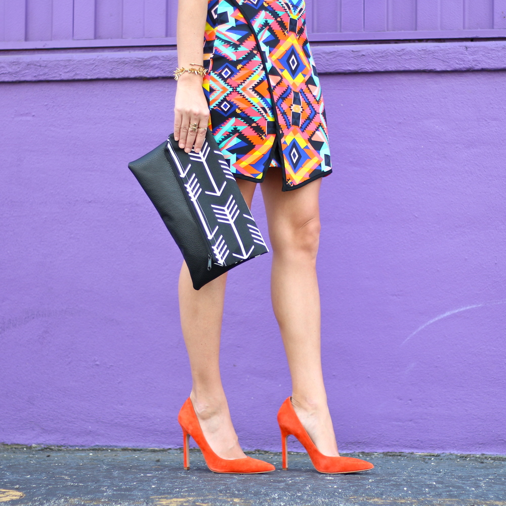 Asymmetrical tribal print dress, arrow clutch, orange pumps