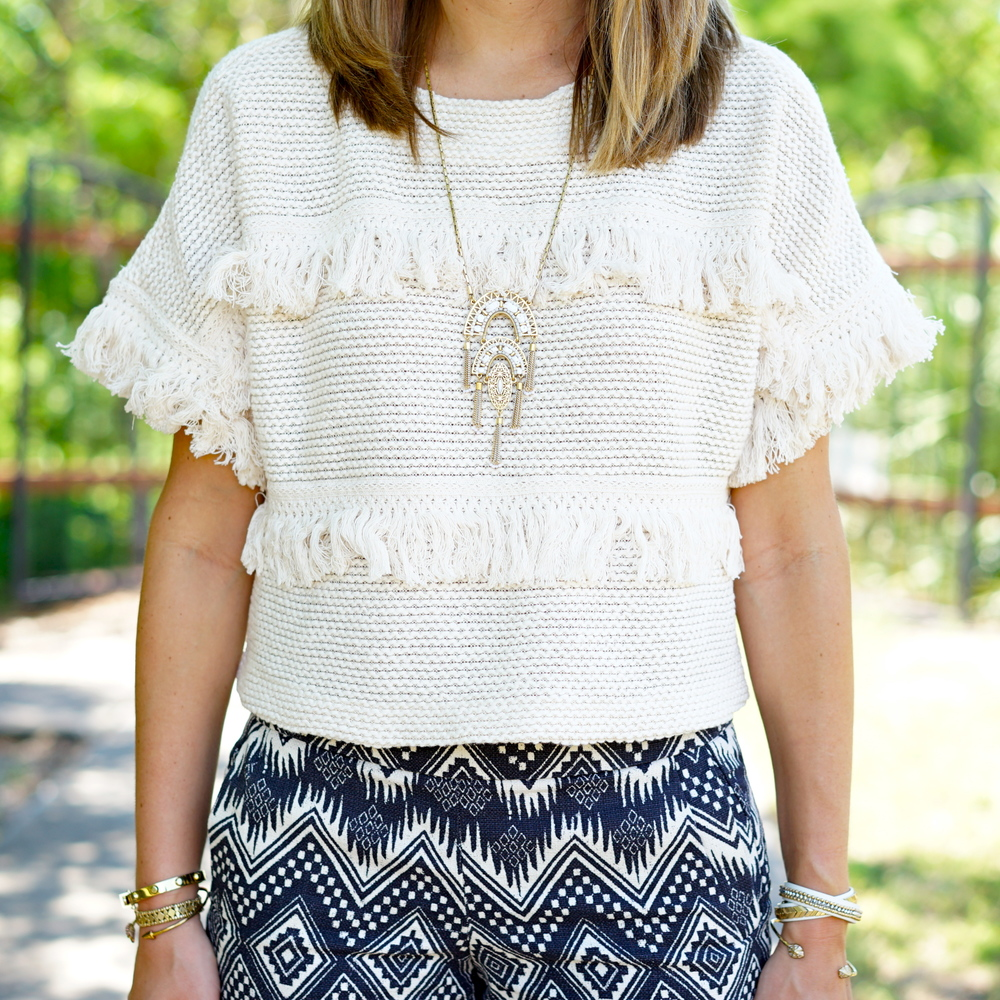Fringe sweater, ivory pendant, printed shorts