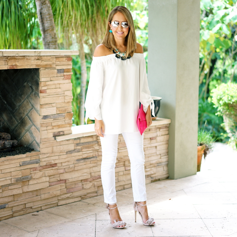 White off shoulder top, white jeans, hot pink clutch