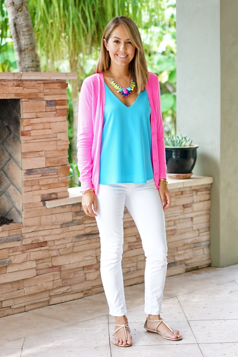 Neon pink cardigan, blue tank, statement necklace, white jeans
