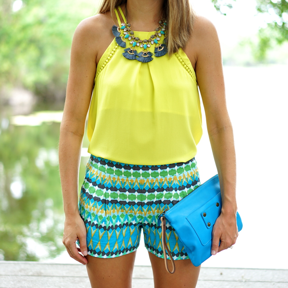 Yellow top, printed shorts, blue clutch, fringe necklace