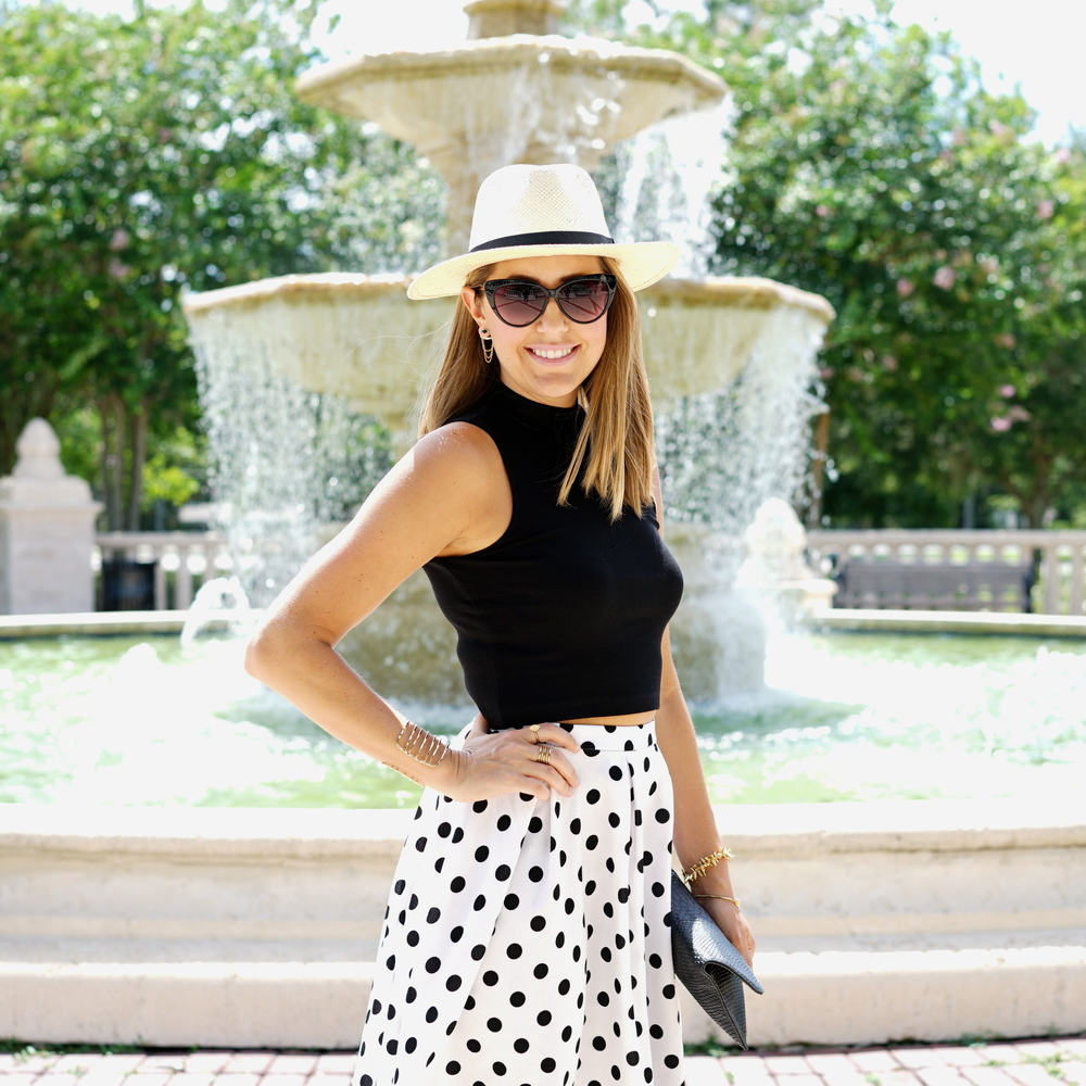 Panama hat, black sleeveless turtleneck, full polka dot skirt