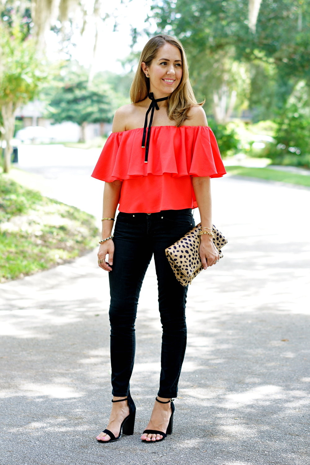 Red top, black jeans, leopard clutch