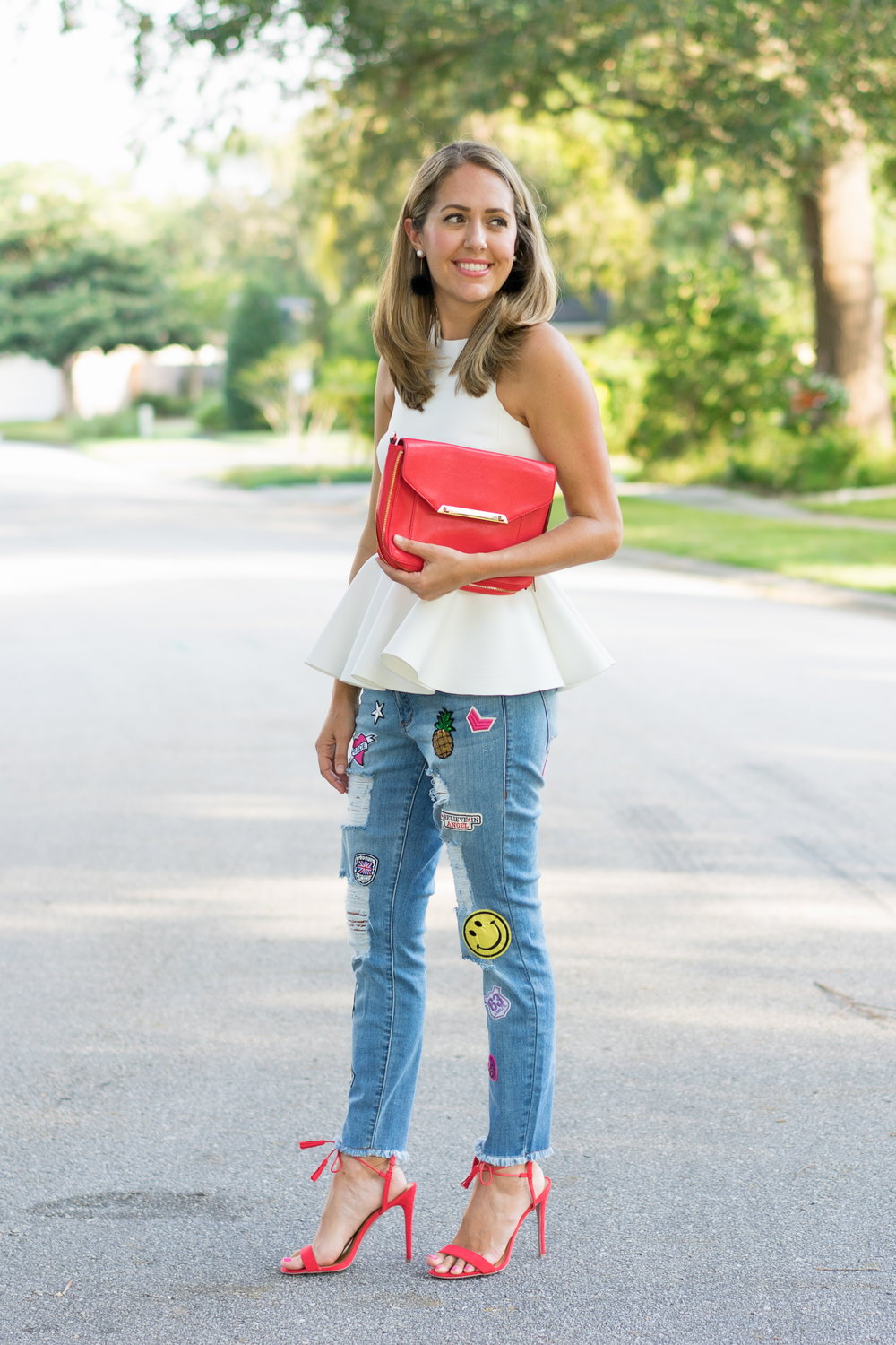 White peplum top with patch jeans and red heels