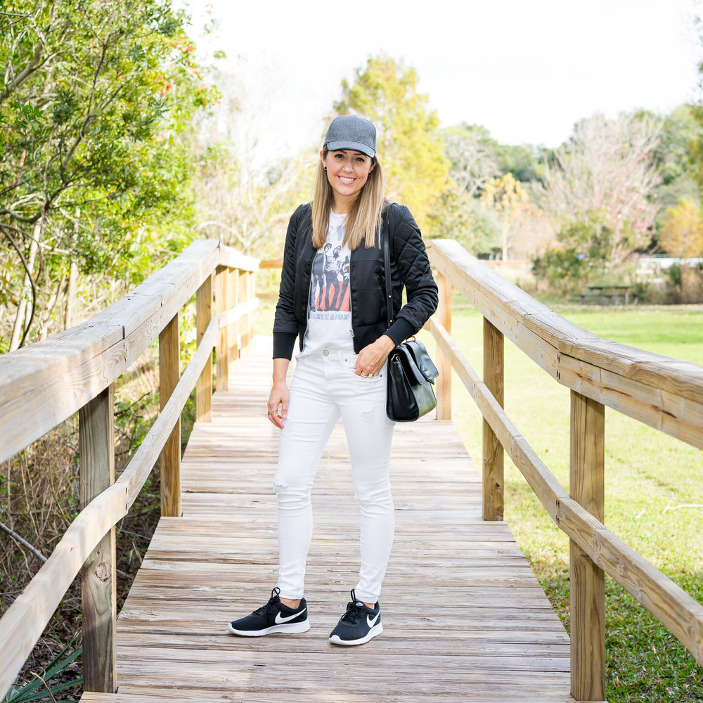 Baseball hat, graphic tee, bomber jacket, white jeans, Nike Tanjun