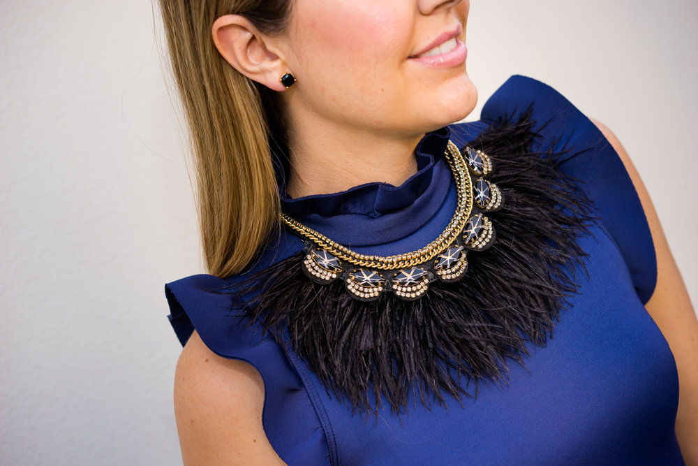 Navy dress, black feather necklace