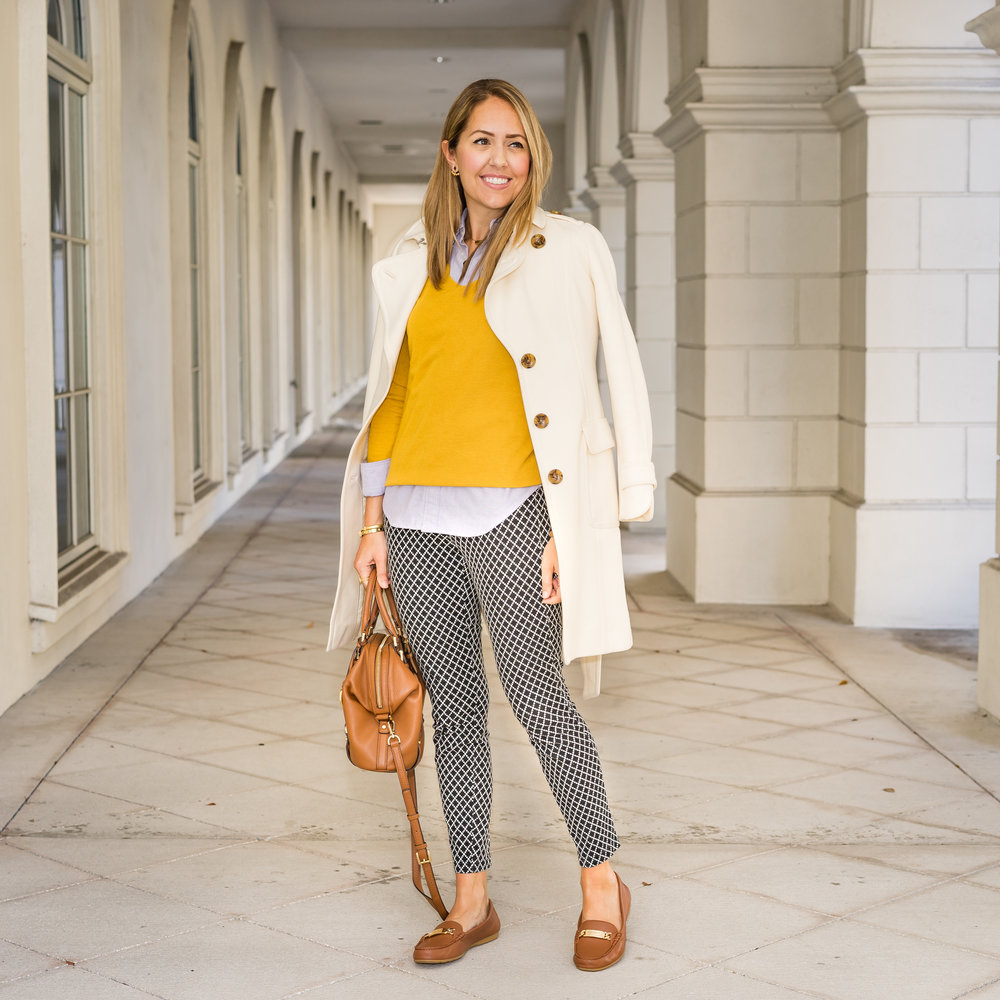 Ivory coat, oxford top, mustard sweater, printed pants