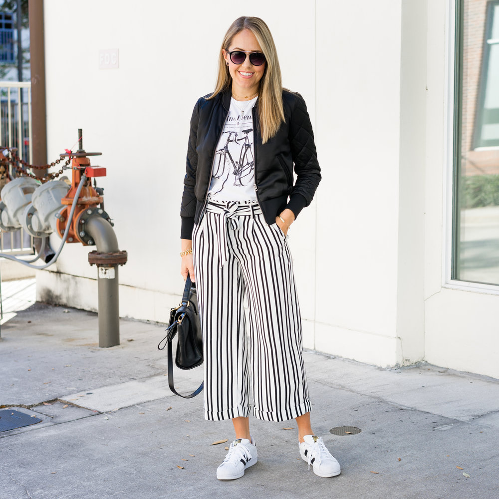 Bomber jacket, graphic tee, stripe pants, Adidas sneakers