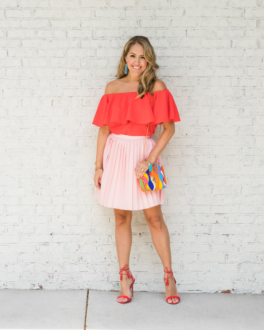 Red ruffle top, peach pleated skirt, colorful clutch