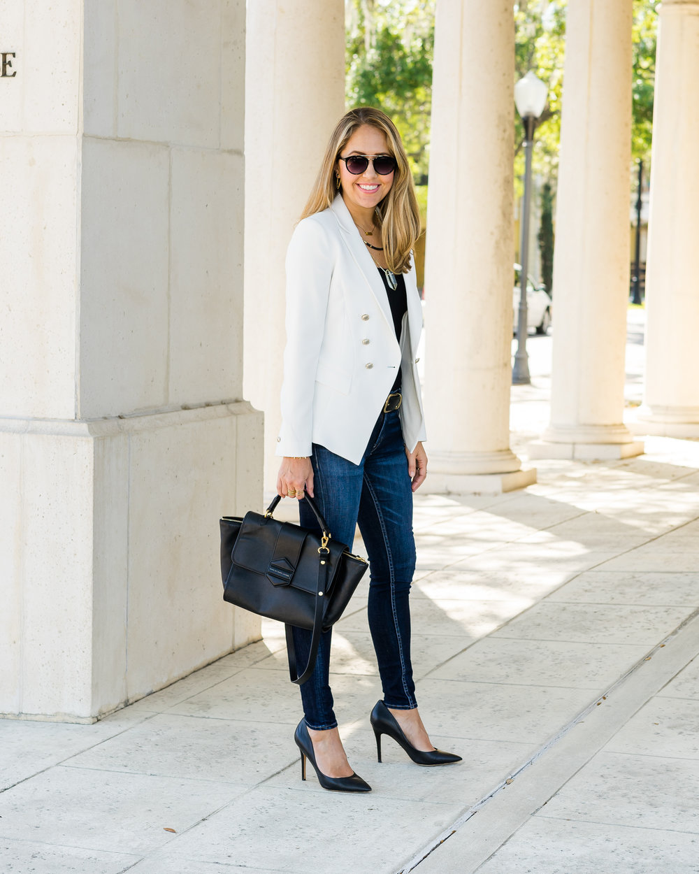 White blazer, black top, layered necklaces