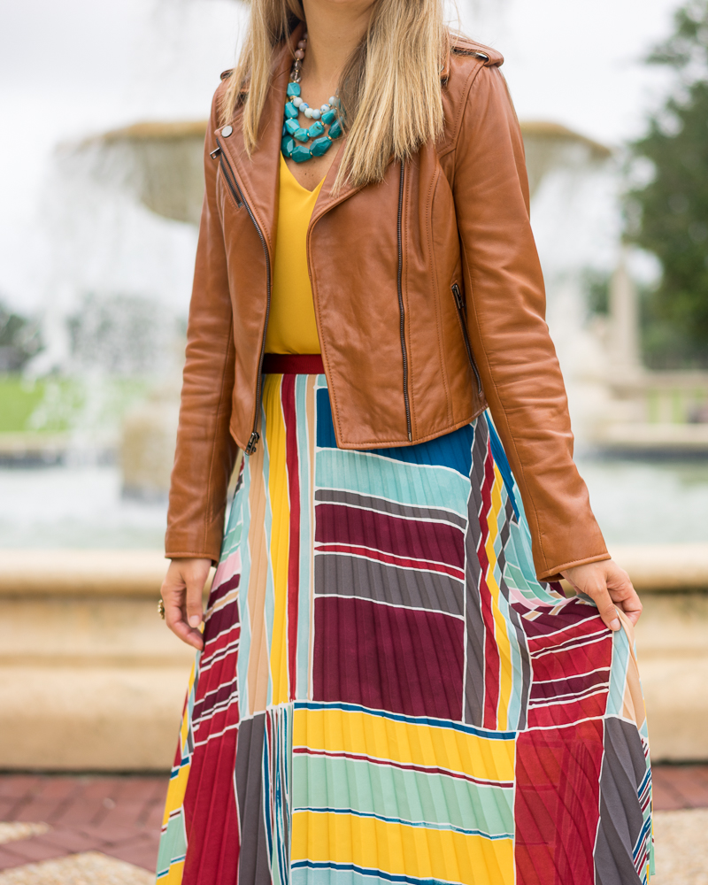 Yellow top, pleated maxi skirt, turquoise necklace, brown leather jacket