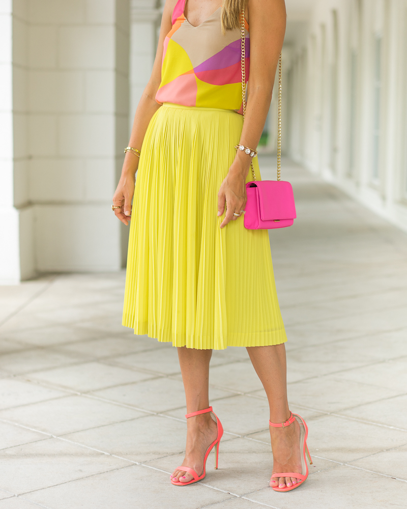 Trina Turk top, pleated yellow skirt, pink purse