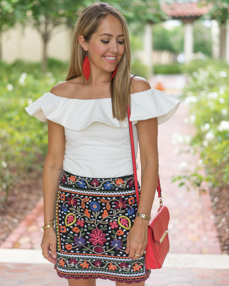 Embroidered skirt, white ruffle top, red earrings
