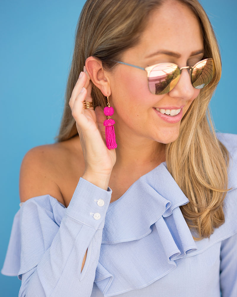 Blue ruffle one shoulder top and pink tassel earrings
