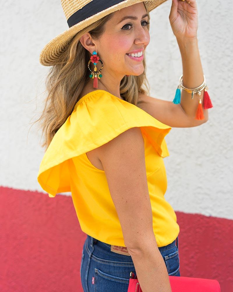 Yellow ruffle top, J.Crew statement earrings, red clutch